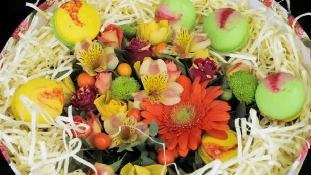 Bright bouquet of flowers and macaroon gift box, close-up