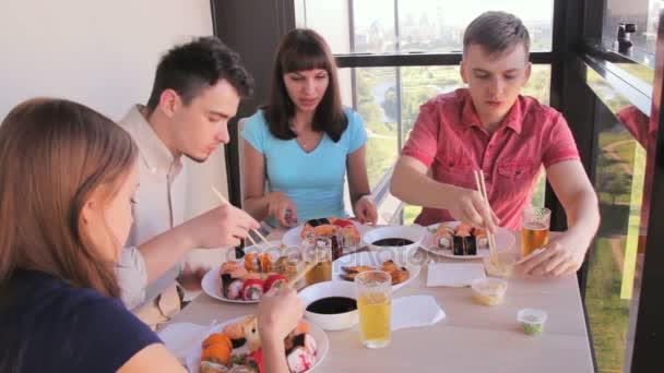 Zwei Paare von Freunden, asiatisches Essen mit Stäbchen auf der Terrasse zu essen