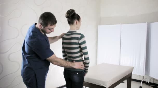 Arzt manuelle Therapeut tastet Patienten Wirbelsäule Mädchen