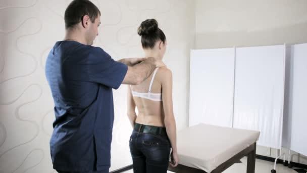 Manuální terapeut doktor zkoumá dívka páteře u pacientů