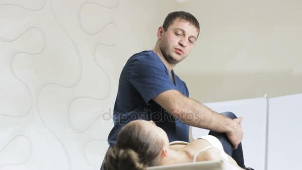 Chiropraxe lékař se ptá na bolesti v kloubech nohy pacienta mladá dívka