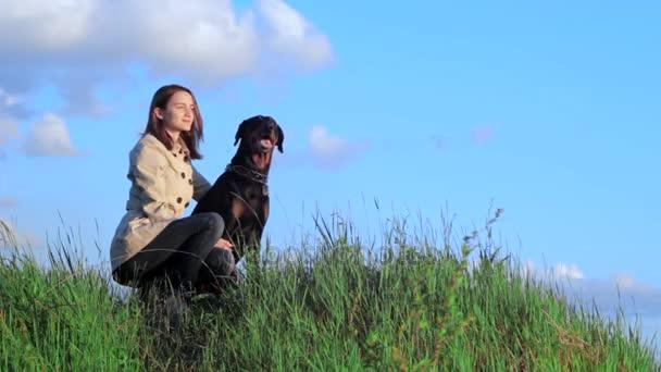 Mädchen mit Hund Dobermann auf einem grünen Hügel