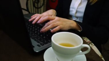 Women hands print the text on a laptop keyboard with a Cup of green tea