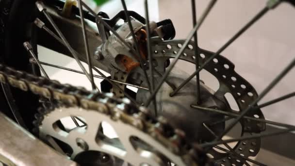 Exhibition of motorcycles, The rear wheel of the motorcycle spinning closeup, brake disc and chain