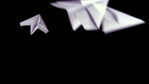 große Anzahl von Papierflugzeugen auf schwarzem Hintergrund