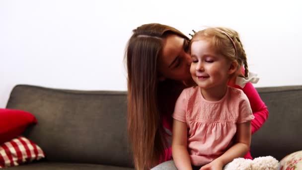 Mladá maminka šeptá jí do ucha dcery tajemství