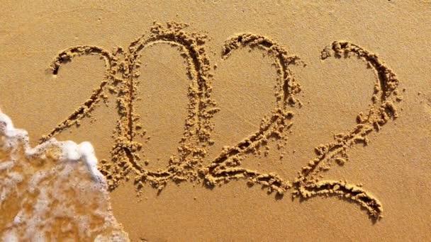 Text 2022 namalovaný na písku smývá vlna