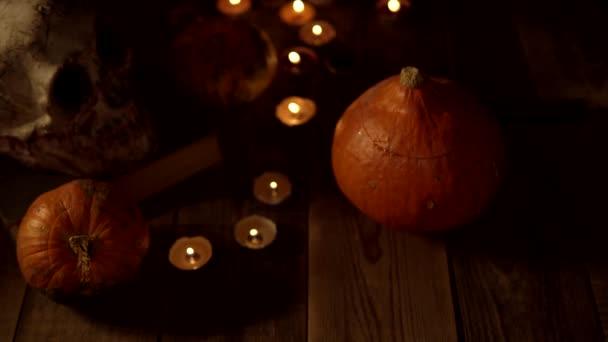 Zátiší dýní a lebek na dřevěném stole, když zhasnou svíčky