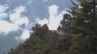 Tourists walk along a high mountain trail