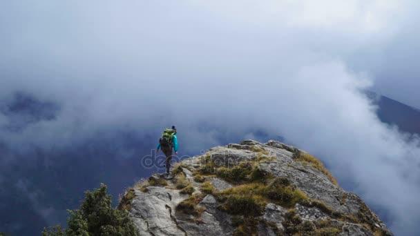 Dívka s batohem dosahuje až nahoru na horu a zvedl ruce