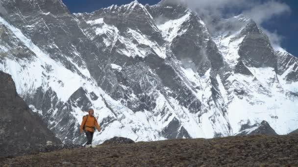 Muž s batohem šplhá v Himalájích