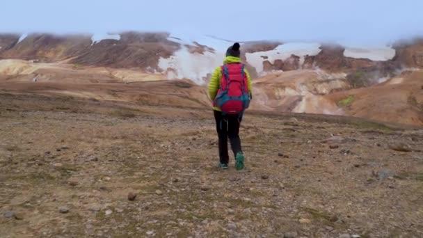 Žena s batohem kráčí po horách