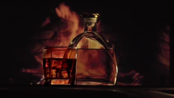 Láhev a sklenice alkoholu u krbu