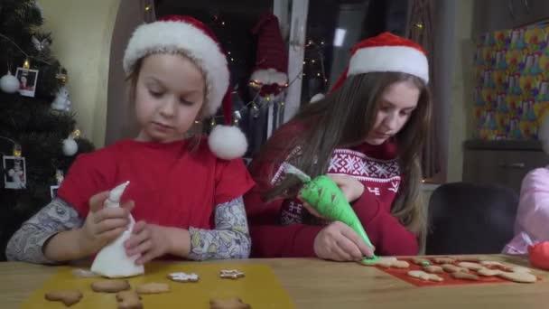 Kinder schmücken Weihnachtsplätzchen