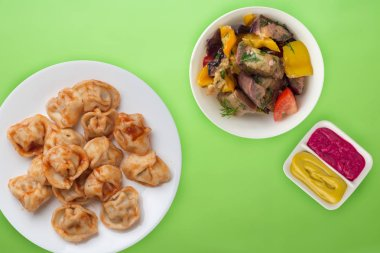 dumplings on a white  plate against a colored background. Dumpli