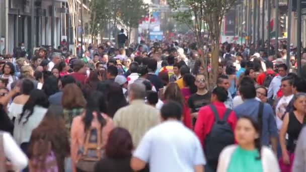 Crowd walking through street.