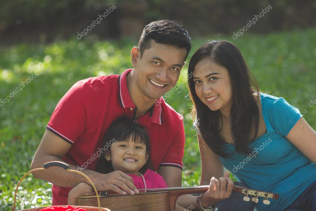 Happy smiling Asian family outing, portrait over green natural background