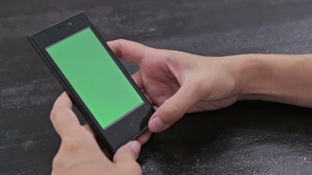 Frau blickt auf Smartphone mit grünem Bildschirm