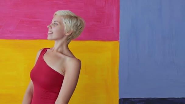 Krásná a mladá blond žena v červených šatech bez make-up při pohledu na fotoaparát
