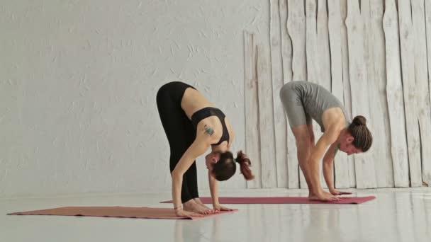 Sportovní muž a žena, která dělá ashtanga jóga
