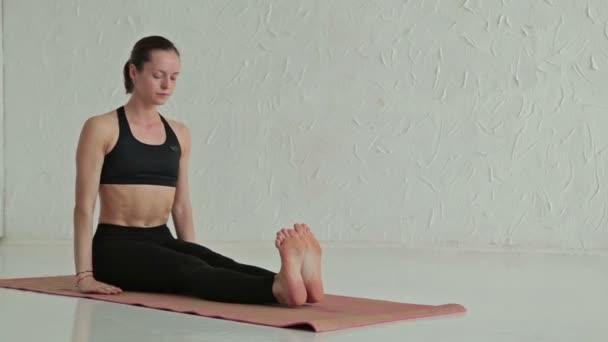 Mladá sportovní žena cvičí jógu - šalvěj marici kroucení póza, marichyasana