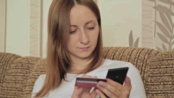 junge Kaukasierin kauft auf ihrem Smartphone Waren aus dem Internet