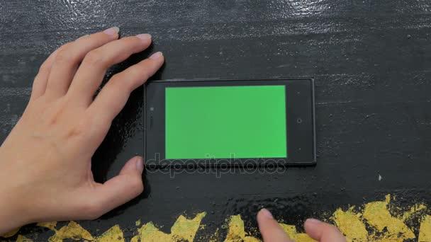 Nő használ okostelefon zöld képernyővel