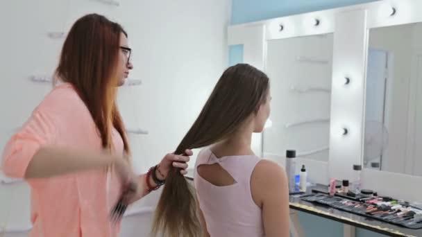 professioneller Friseur frisiert junge hübsche Frau mit langen Haaren
