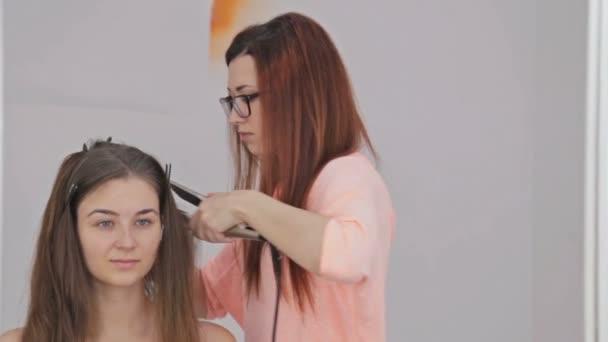 Pomocí žehličky na vlasy dlouhé žena v kadeřnictví kadeřník