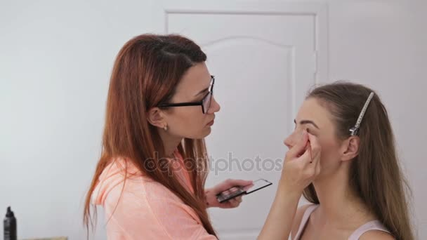 2 shots. Professional make-up artist applying eyeshadow