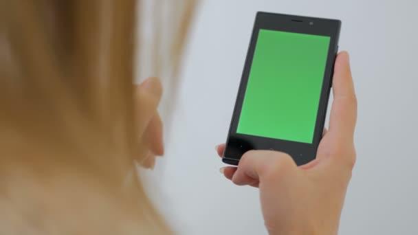 Žena používající smartphone s zeleným plátnem