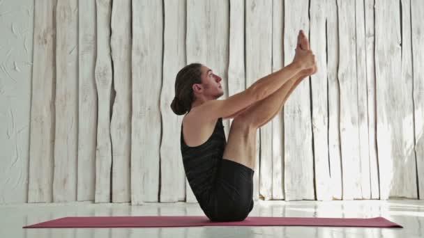 Sportlicher junger Mann praktiziert Yoga im Fitnessstudio