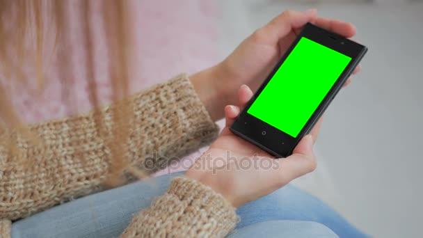 Žena při pohledu na smartphone se zelená obrazovka