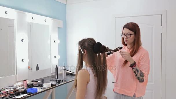 Profesionální kadeřník dělá účes pro Mladá krásná žena - dělat lokny