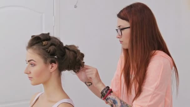 Hairdresser finishing hairstyle for young pretty woman