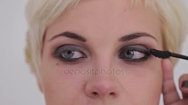 Professional make-up artist applying mascara on eyelashes of model