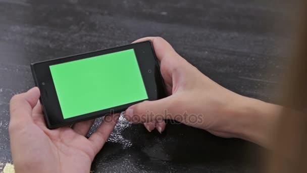 Donna che esamina smartphone con lo schermo verde