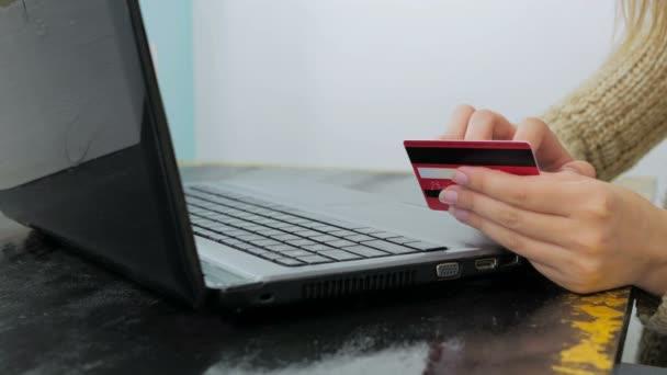 Frau kauft online am Laptop mit Kreditkarte ein