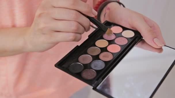 Make-up artist taking eye shadows from makeup eyeshadows palette