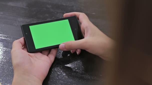 Donna che utilizza smartphone con schermo verde