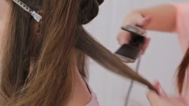 2 výstřely. Pomocí žehličky na vlasy dlouhé žena v kadeřnictví kadeřník