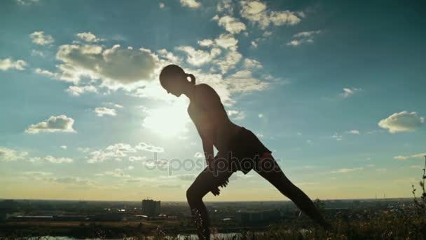 Žena cvičí jógu v parku při západu slunce - hrdina pozice Virabhadrasana