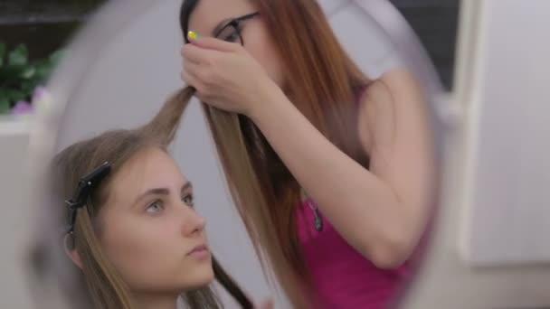 Profesionální kadeřník dělá účes pro Mladá krásná žena