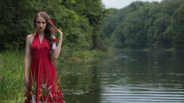 Tajemná dívka s kreativní make-up v etnické červených šatech chůze ve vodě