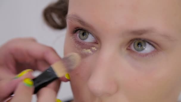 4 shots. Professional make-up artist applying cream base eyeshadow primer to model eye