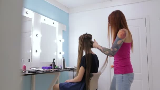 Professional hairdresser doing hairstyle for young pretty woman - making curls