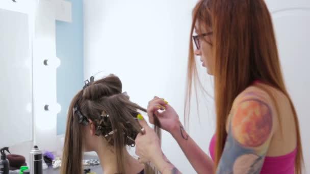 2 výstřely. Profesionální kadeřník dělá účes pro pretty dospívající dívka