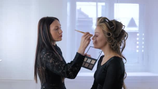 Professzionális sminkes smink alkalmazása a womans arc