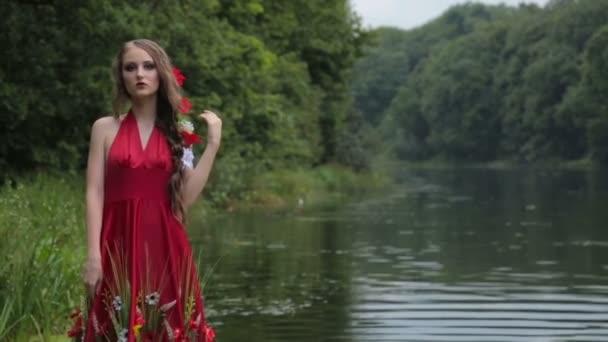 2 výstřely. Tajemná dívka s kreativní make-up v etnické červených šatech chůze ve vodě