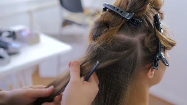 Používání žehličky na dlouhé vlasy klienta v kadeřnictví kadeřník